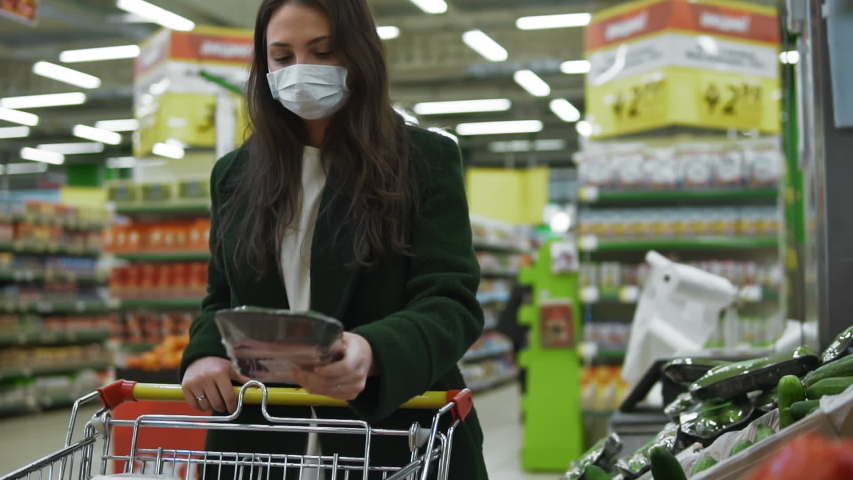 Woman wearing protective medical face mask buys food at supermarket or grocery shop. Female customer puts vegetables in shopping cart. Quarantine and isolation during covid-19 coronavirus pandemic | Shutterstock HD Video #1051703902