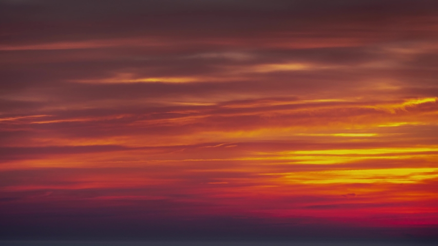 Panning down aerial timelapse of a beautiful soft and feathery pink, orange, blue and yellow sky sunrise reflecting on the water of Lake Michigan in Chicago with tree lined shoreline below.