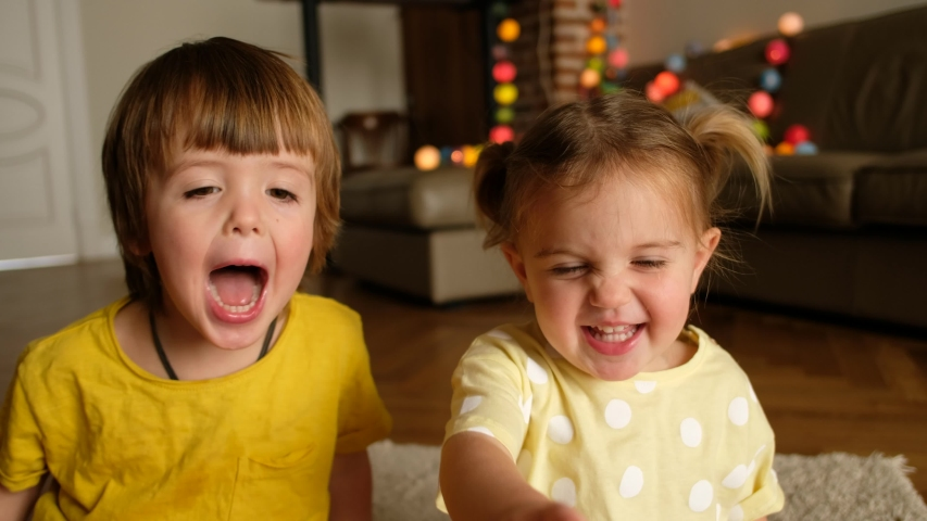 Happy cute children make faces and laugh while looking at the screen. Kids smiling and looking at camera while playing on blurred background of living room | Shutterstock HD Video #1051717285