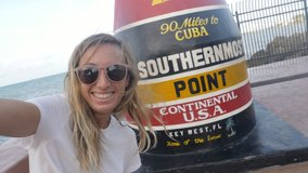 Woman taking selfie with Southernmost point in Key West USA.Cheerful blond hair girl taking selfie portrait video chatting online sharing vacations
