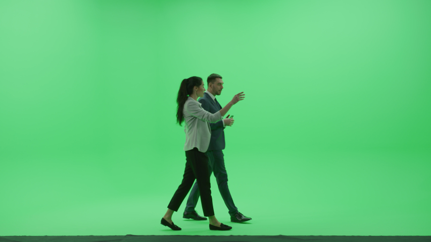 Chroma Key Studio: Beautiful Woman wearing Business Casual Talks with Handsome Businessman, They Discuss Business, Financial Consulting and Walking Across the Green Screen Room. Side View Shot