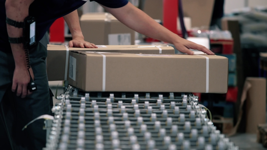 Parcels are scanned on the packaging line in a warehouse. Parcels wait on the conveyor to be shipped. Automation of online shipping logistics Royalty-Free Stock Footage #1051730782
