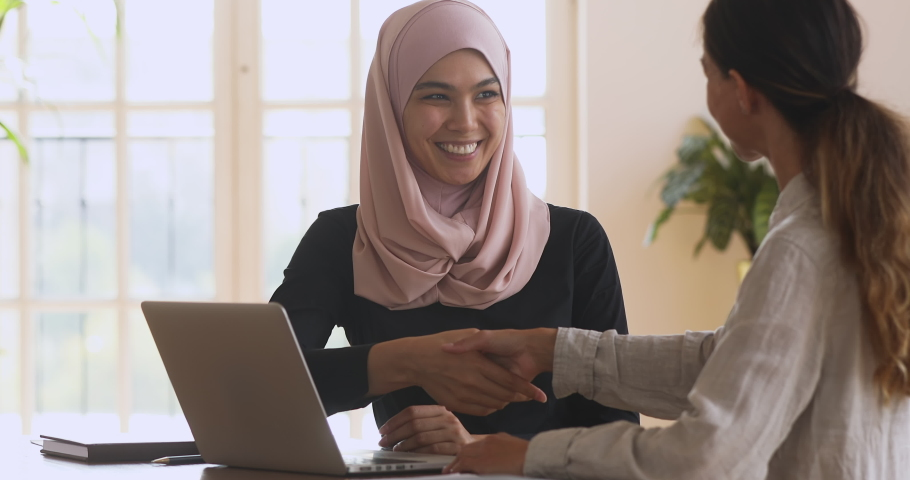 Smiling young asian muslim woman in hijab showing presentation on computer to female partner client, shaking hands making agreement, thanking for help, establishing partnership in modern office. Royalty-Free Stock Footage #1051730911