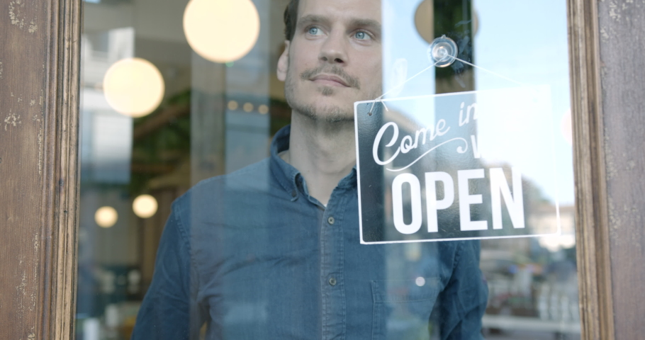 Small Business owner man in apron hanging open sign on door smiling welcoming clients to new cafe restaurant. Entrepreneur Service hospitality.