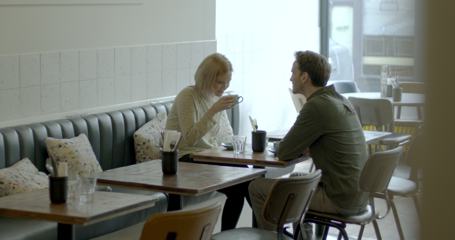 Young Adult couple having a good time together in cafe restaurant and drinking coffee at table