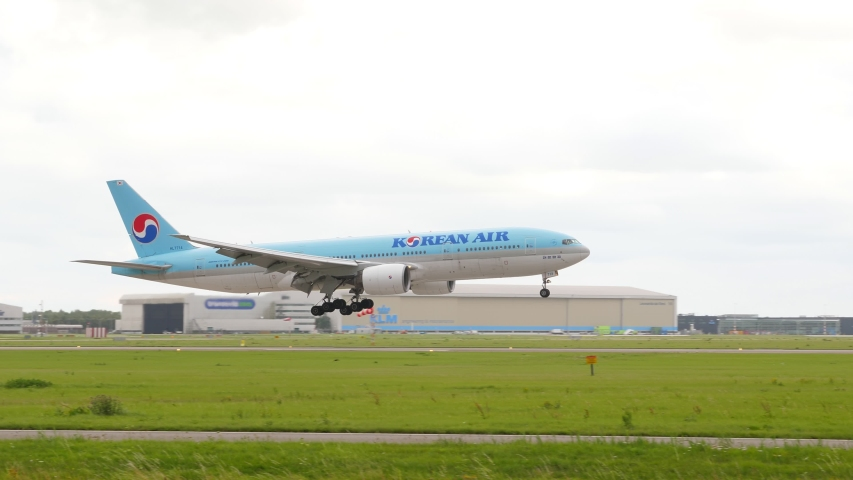 AMSTERDAM - AUGUST 15, 2019: Korean Air Boeing 777 landing moment, spotting at Amsterdam Airport Schiphol. Large passenger jet move low and touchdown runway with white smoke from gear tires
