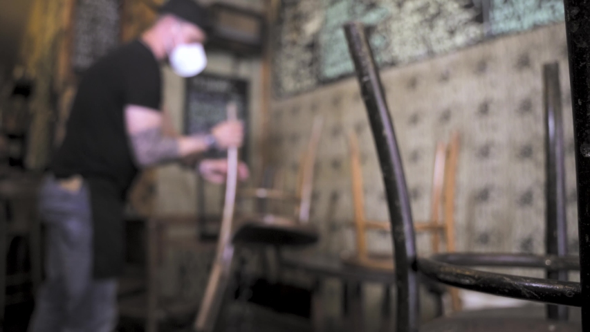 Reopening of a coffee shop or bar after the covid-19 emergency. A waiter or a male cafeteria owner takes the chairs off the table.The lockdown and quarantine ended but still wearing medical mask.   Shutterstock HD Video #1051739392