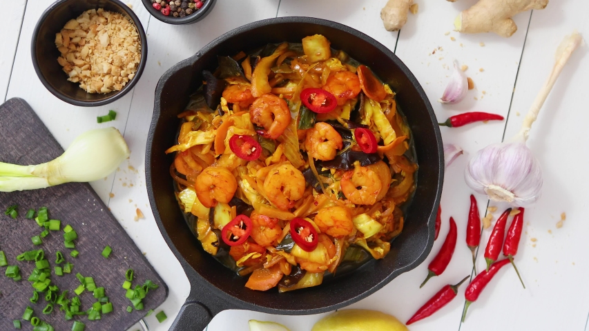 Fresh fried noodles with vegetables with shrimps served in black iron pan. With various ingredients on side. White wooden background. Top view. Slow motion spin video. Royalty-Free Stock Footage #1051741396