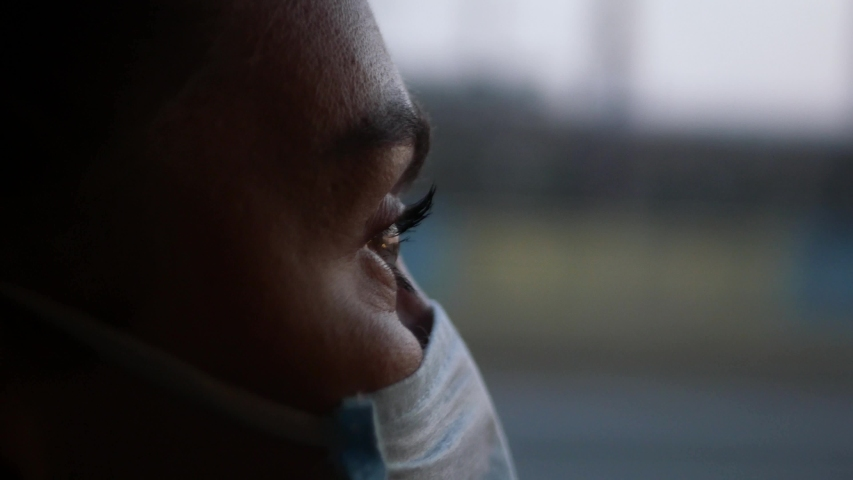 A young Woman in a protective mask rides public transport and looks out the window. Portrait of a woman in a protective mask on a social bus. Pandemic COVID-19. Social distance. Royalty-Free Stock Footage #1051748686