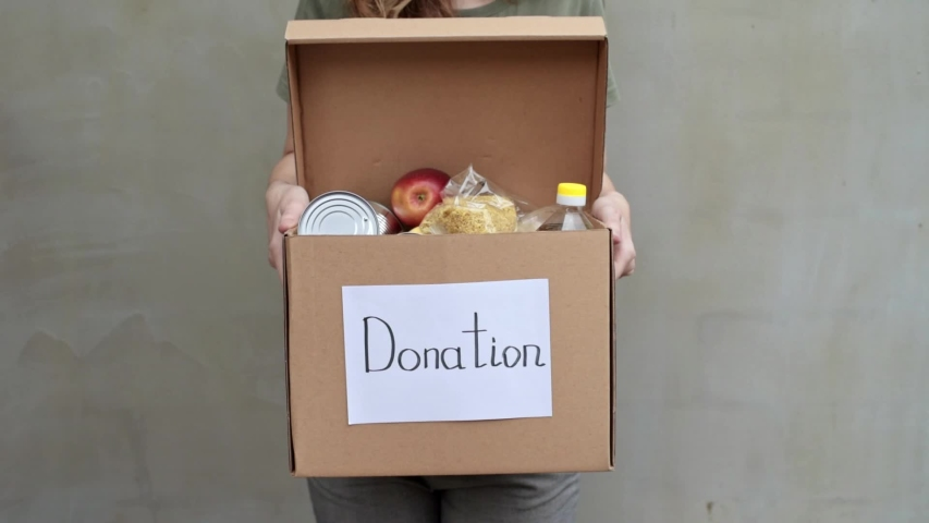Woman volunteer hold donation box with food against gray background. Donations and charity concept