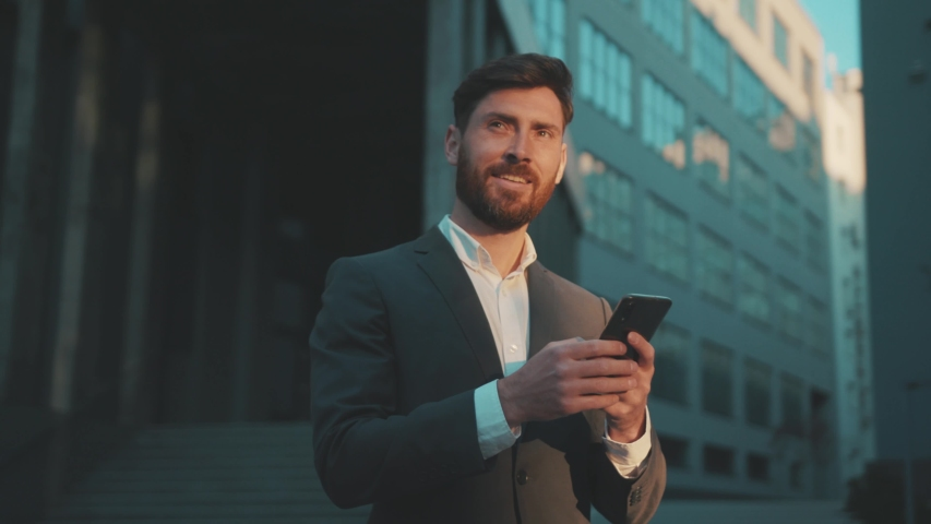 Shot move around businessman stand in the city center street uses phone texting scrolling tapping smile technology communication sunny day success slow motion Royalty-Free Stock Footage #1051756645