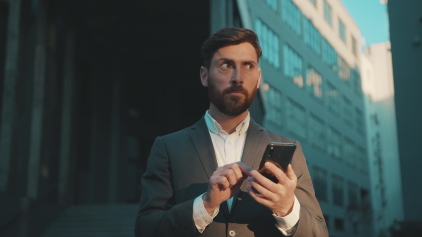 Handsome happy man stand in the city center street uses phone texting scrolling tapping smile technology communication sunny day success slow motion | Shutterstock HD Video #1051756657