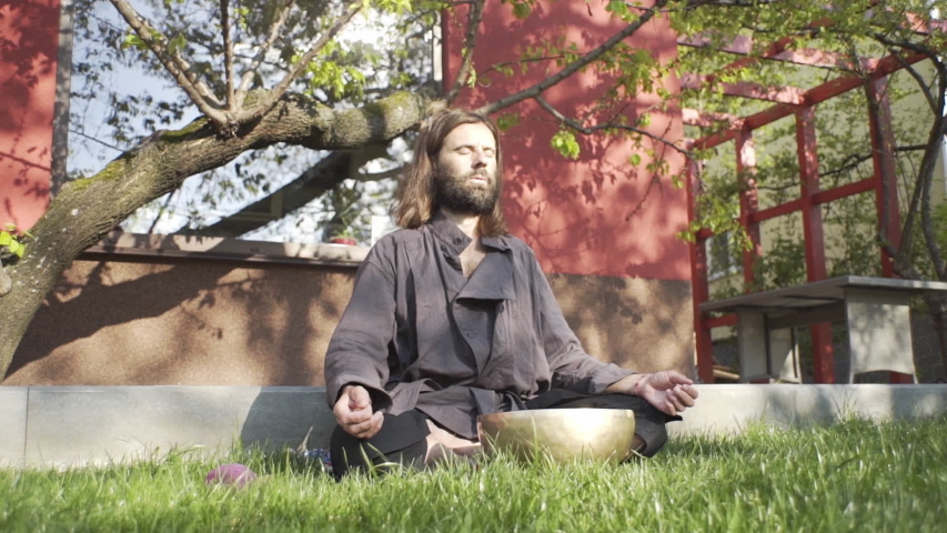 A qigong master conducts meditation using a gong and Crystal bowl, Crystal Tibetian singing bowl, a master meditates receives energy for the body | Shutterstock HD Video #1051757896