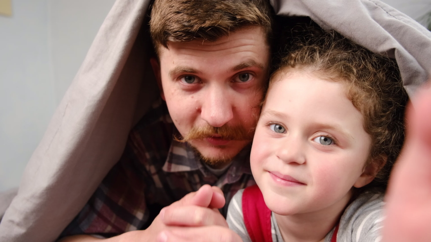 Happy dad and cute little kid child daughter lying on bed covered with blanket talking video calling on chatting laughing enjoy online conversation looking at webcam, family vloggers recording video Royalty-Free Stock Footage #1051798726