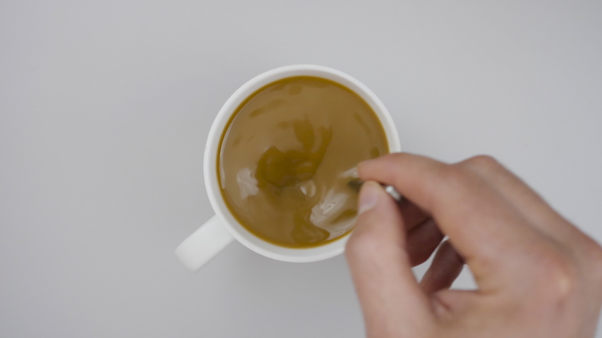 Male hand cup of Hot coffee Closeup Top view. Business and Drink Concepts. Top view of person hand stirring coffee with spoon on gray wooden table. Close up. Slow Motion.   Shutterstock HD Video #1051802659