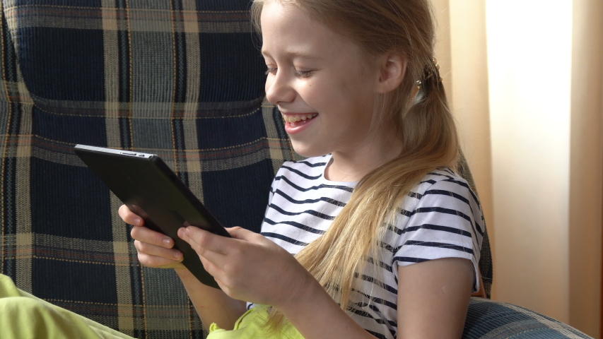 Funny little girl smiling looking at camera, stay at home, cute kid talking to webcam making online video call or recording vlog having fun. Royalty-Free Stock Footage #1051809076