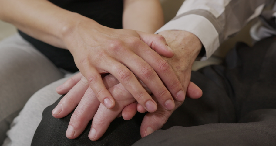 A young womans hands comforting a old man hands. Closeup.