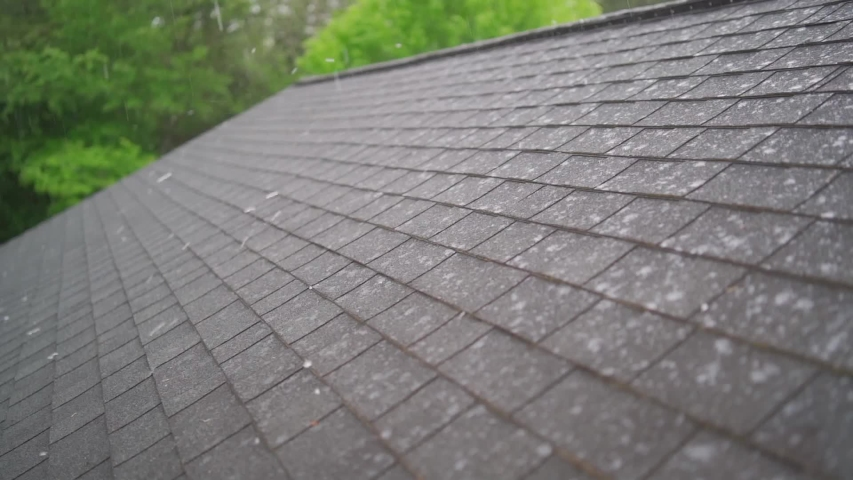 Slow Motion of hail storm hitting roof shingles causing roof damage in summer thunderstorm of severe weather. Royalty-Free Stock Footage #1051820998