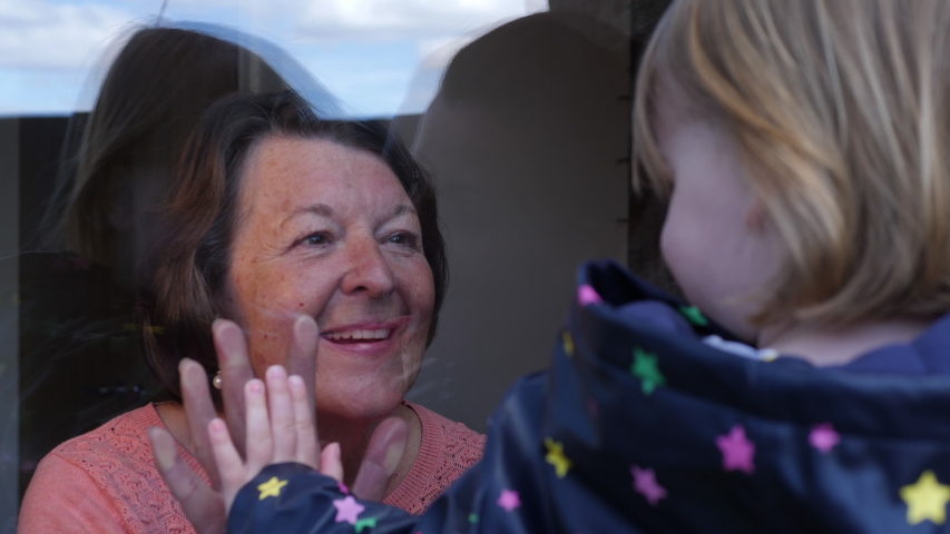 4K: Grandma seeing her Family through the window during Lockdown - Social Distancing during the COVID-19 Coronavirus Outbreak. Stock Video Clip Footage