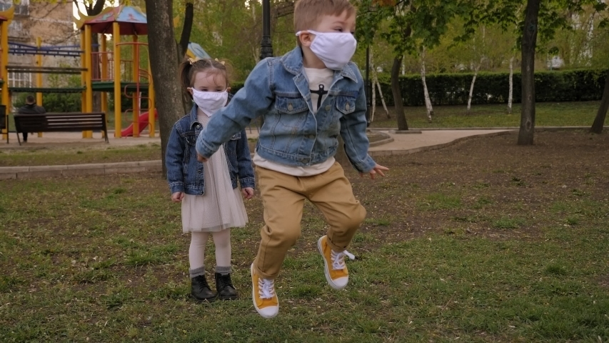 Two cheerful little children in medical masks are playing on the street in the Park, they are jumping on the background of the Playground. Quarantine for the coronavirus. Covid-19 pandemic outbreak. | Shutterstock HD Video #1051826275