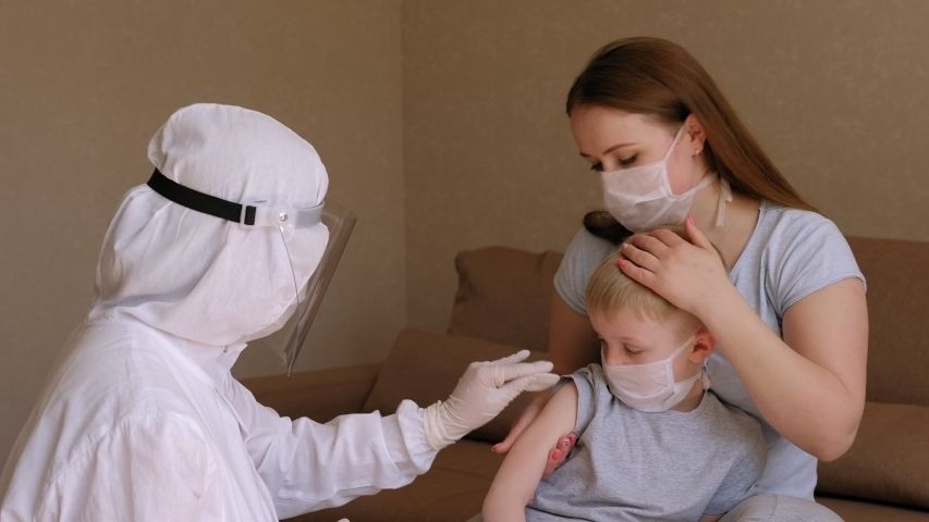 A doctor in a protective suit and mask is preparing to give an injection to a young boy at home, a family with symptoms of coronavirus is in quarantine. Vaccination against coronavirus at home. | Shutterstock HD Video #1051826290