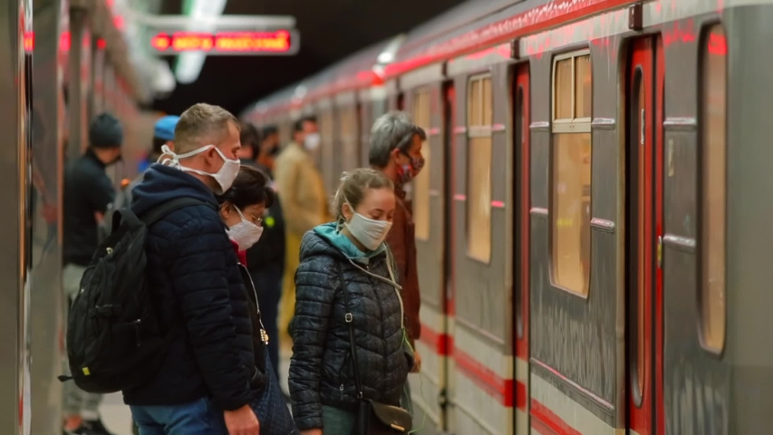 Passengers in protective masks on their faces enter the subway car of public transport. Respiratory protection in a public place. People during quarantine COVID-19  CZ, Prague, Veleslavin, 10.4.2020.
