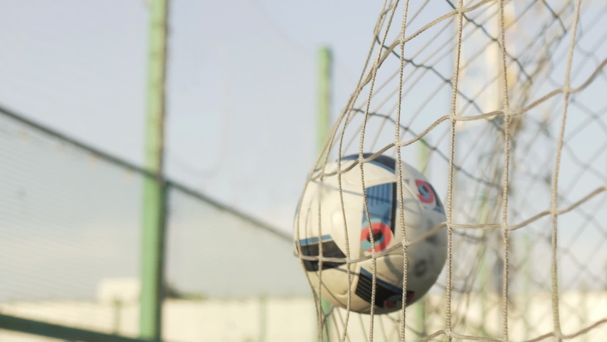 Slow Motion of soccer ball flying into Goal Net of gate. Close up Sport and football game concept. Camera Shot from Behind Net. Soccer player kicking ball into goal | Shutterstock HD Video #1051833856