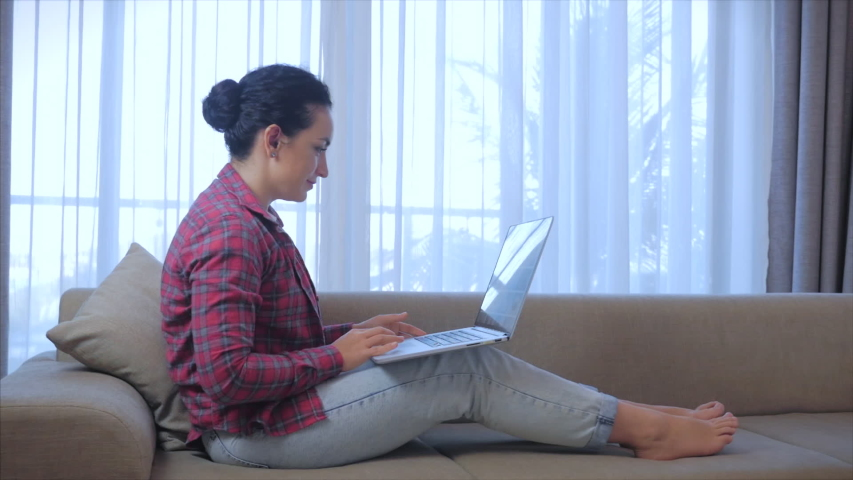 Young serious woman freelancer working on a laptop sitting on a sofa at home, businesswoman typing on a laptop, focused girl using a computer to study online work at home. Home clerk work concept Royalty-Free Stock Footage #1051866952