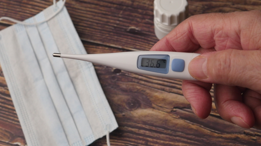 Electronic Thermometer Shows A Temperature Of 36.6 Degrees Celsius, A Man Holds An Electronic Thermometer On The Background Of The Table. On The Table Is A Medical Protective Mask And Medication.	 | Shutterstock HD Video #1051874725