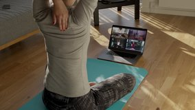 Fitness coach teaching yoga online to group of people. People practicing yoga with trainer via video conference.