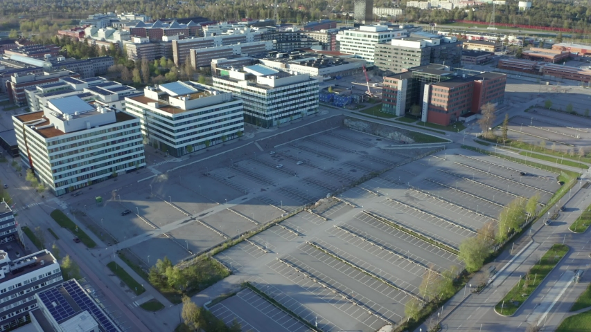 Drone shot of empty parking lot in front of shut down closed office buildings due to Corona virus pandemic. Aerial shot of free stalls with white painted lines car parking space. home office effect Royalty-Free Stock Footage #1051893550