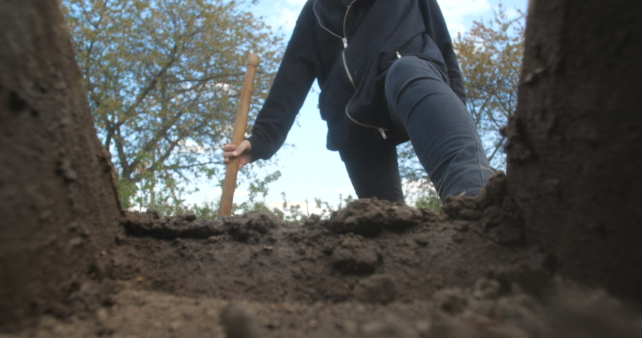 An unrecognizable person in dark clothes is digging a square pit against a blue sky with clouds. Point of view from the grave into which soil is sprinkled from a shovel. Slow motion 50 fps 4k Royalty-Free Stock Footage #1051898743