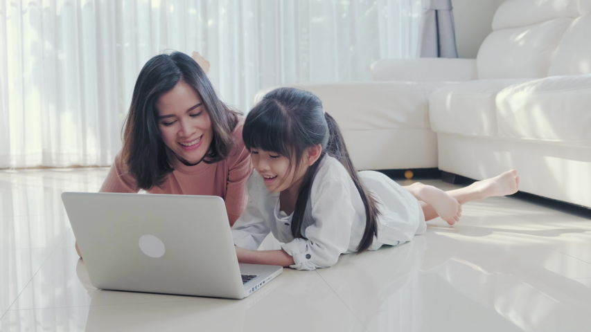 Asian family learning from home together. Young girl kid studying education class with mother in living room. Woman and child laughing and feeling fun, enjoy learn and play subject in computer laptop.