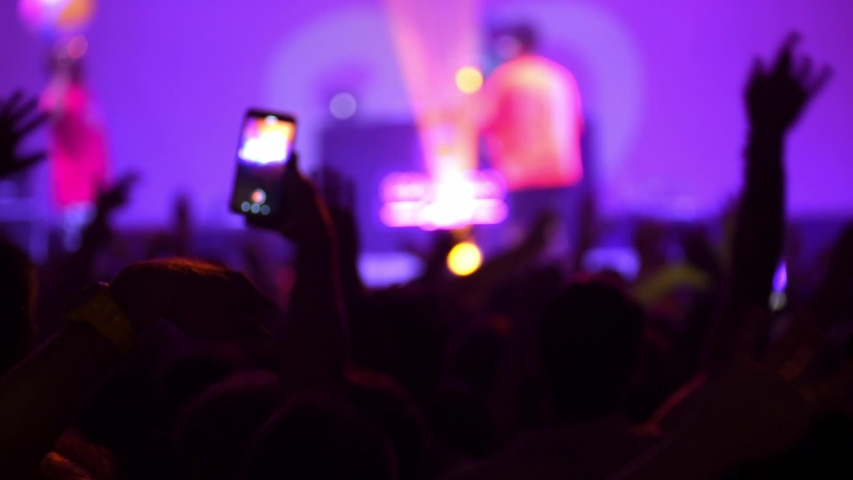 Happy people are watching an amazing musical concert. Merry fans jump and raise their hands up. Crowd of excited fans applauding to popular band performing favorite song. A group of fans with phones | Shutterstock HD Video #1051914112