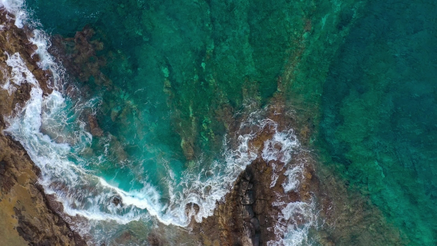 Top view of a deserted coast. Rocky shore of the island of Tenerife. Aerial drone footage of ocean waves reaching shore. Camera is spinning