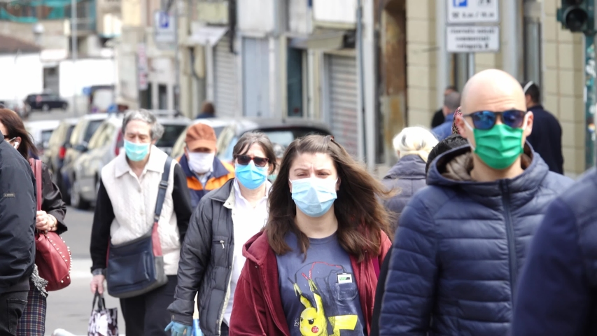 Coronavirus outbreak lifestyle: people walking down the street wearing coronavirus masks Turin, Italy - April 2020