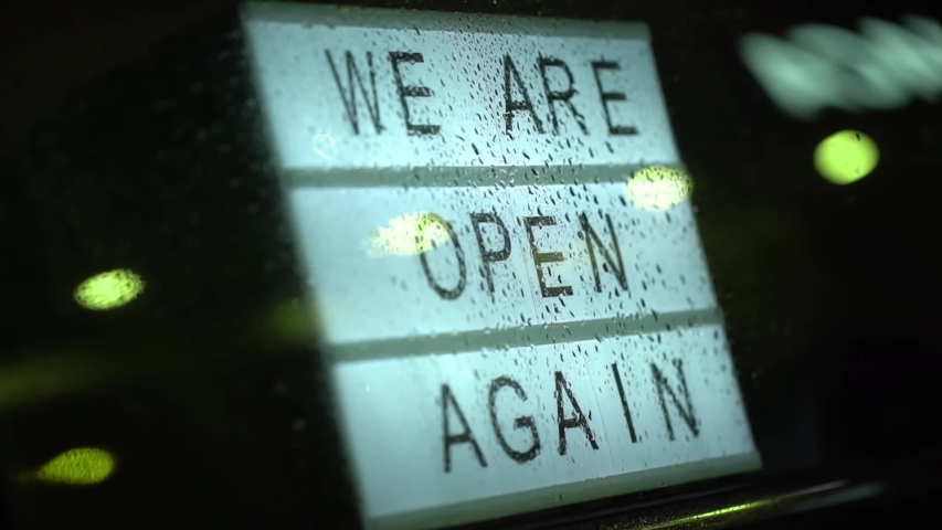 Lightbox with a sign we are open again behind a glass door of the cafe during the rain in the evening. We're open again after quarantine, video of small business owner. Please wear a face mask   | Shutterstock HD Video #1051920595