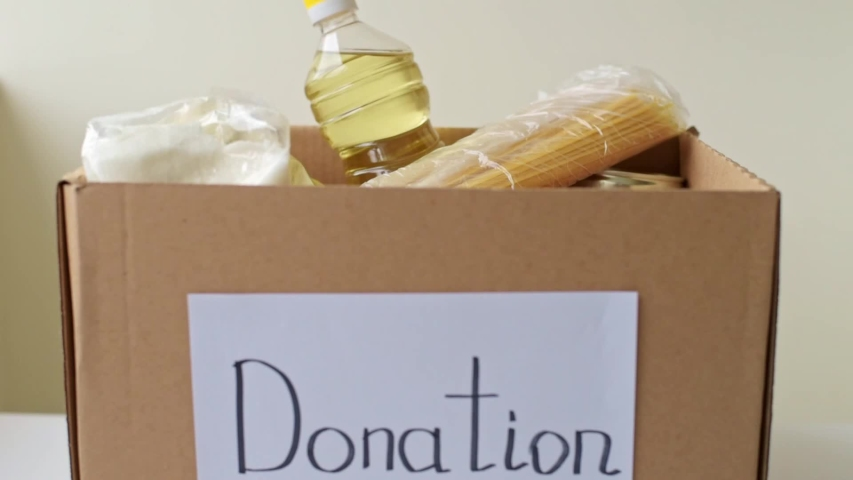 Volunteer hand puts food in a box with donations. Charity and donation concept