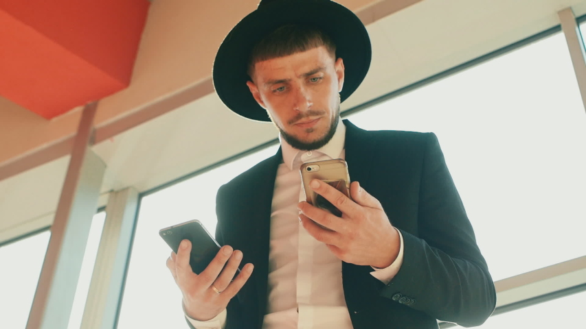 Man wearing black suit and hat with two smartphones in his hands decides his own Affairs. Person looks like Jew or Italian mafia. Low angle shot, bottom view. Businessman with beard and mustache | Shutterstock HD Video #1051945372