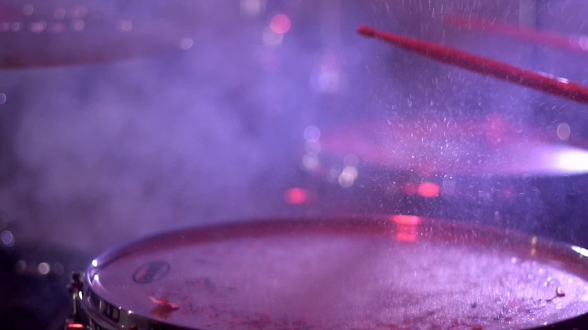 Beat drumsticks on the drum on which drops of water, a splash. Performance at a concert of a drummer, close-up, slow motion