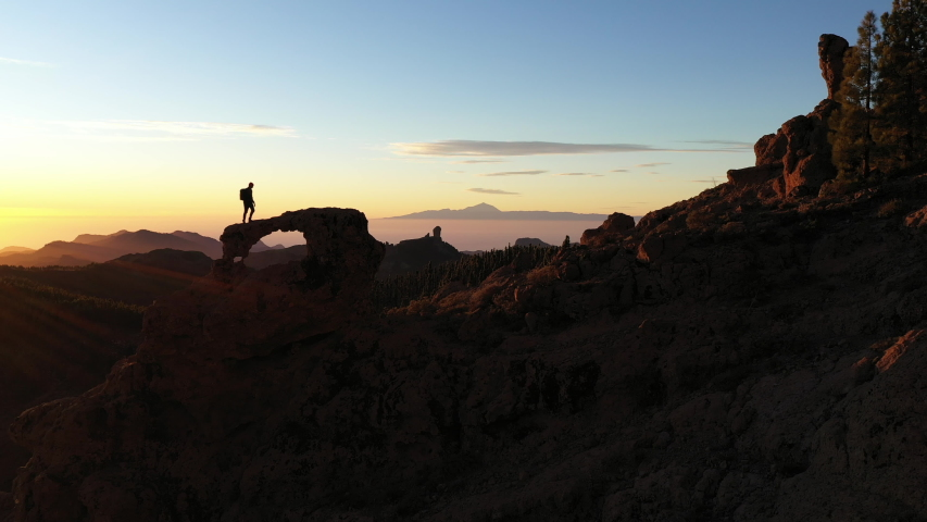 Slow Motion Wide Drone Shot Of Man Walking On Rock Arch Overlooking Mountain Landscape At Sunset   Shutterstock HD Video #1051946920