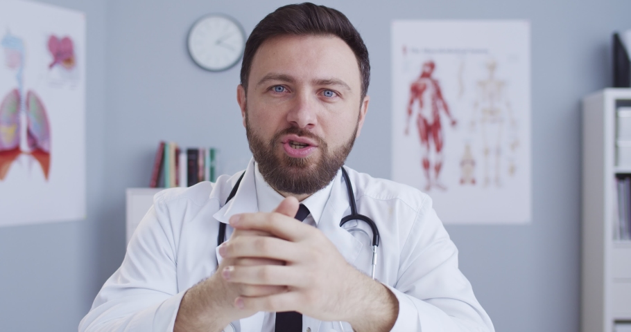 Handsome caucasian male doctor blogger in white robe in clinic office consulting about healthcare online. Man, hospital worker having professional medic consultation on internet during qurantine. | Shutterstock HD Video #1051952764