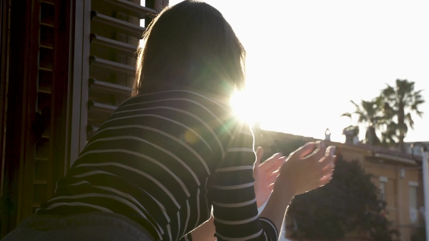 Girl applauds in the window of her room thanking the medical services for covid-19. Sunset in the background. Royalty-Free Stock Footage #1051953253