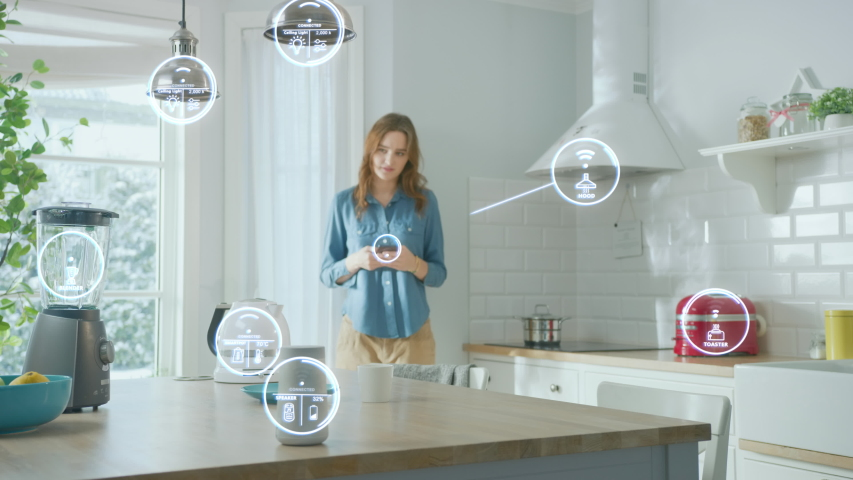 Internet of Things Concept: Beautiful Young Woman Using Smartphone in the Kitchen. She controls her Kitchen Appliances with IOT. Graphics Digitalization Visualization of Connected Home Electronics  Royalty-Free Stock Footage #1051965454