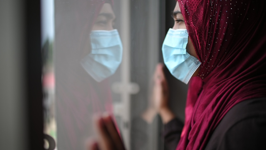 Young beautiful Muslim woman in medical mask and looking outside from glass window to Prevent Disease and Dust, pm.5,Stay at home quarantine coronavirus pandemic prevention. Royalty-Free Stock Footage #1051970668