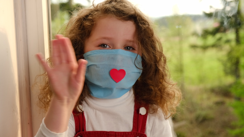 Close up of little girl wearing medical mask with a red heart sitting in windowsill at home vlogger saying hello hi looking at Camera, small kid talking to webcam making online recording having fun Royalty-Free Stock Footage #1051970974
