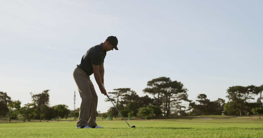 Side view of a Caucasian male golfer on a golf course on a sunny day wearing a cap and golf clothes, swinging a golf club and hitting the ball into the distance, in slow motion  Royalty-Free Stock Footage #1051976302