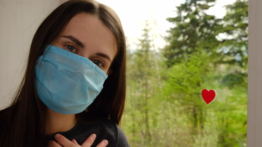 Young woman wearing blue medical face mask sitting on sill with little red heart on window as a way to show thank gratitude to doctors and nurses for help in fight against the disease. Covid-19 | Shutterstock HD Video #1051977112