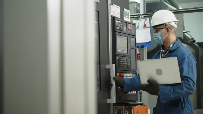Factory engineer check machine equipment. Wear protective equipment. Safety helmet to prevent accidents. Mask to prevent dust or Coronavirus in operation Or industrial factories. Concept new normal | Shutterstock HD Video #1051978408