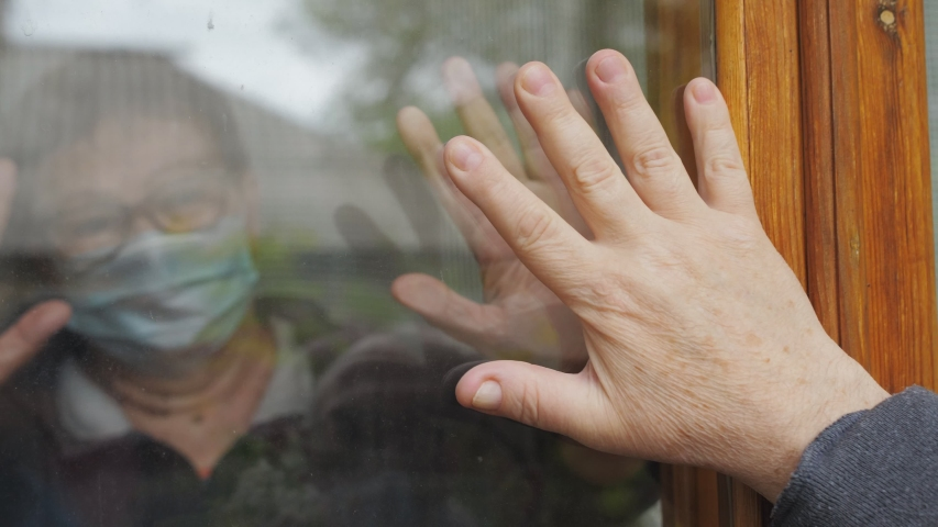 Hands of hope. An elderly man and woman touch the palms of their hands through the glass window that separates them from each other during the strict quarantine period.